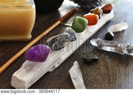 A Close Up Image Of Seven Chakra Healing Crystals Charging On A Selenite Wand.