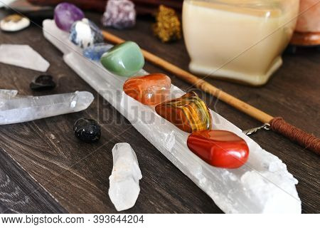 A Close Up Image Of Seven Chakra Healing Crystals Charging On A Selenite Wand.