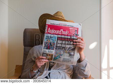 Paris, France - Nov 5, 2020: Woman Reading In Living Room The Latest Aujordhui Newspaper Featuring O