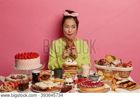 Sweet Temptation. Lovely Asian Woman Enjoys Festive Gathering, Sits At Table With Many Cakes, Bites