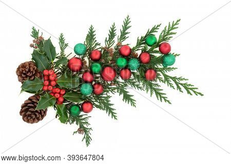 Christmas decoration with holly, cedar cypress, pine cones & red & green baubles on white background. Decorative element for the festive season. Flat lay, top view, copy space.