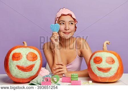 Photo Of Dreamy Pleasant Looking Korean Woman Holds Cosmetic Sponge, Cares About Complexion, Feels F