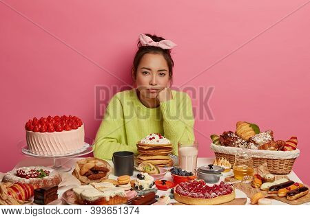 Upset Gloomy Woman Wants To Eat Sweets And Confectionery, Poses At Table Served With Many Desserts,
