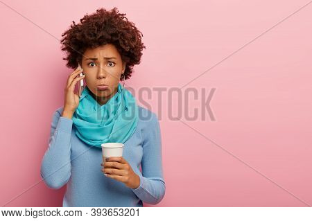 Studio Shot Of Dissatisfied Curly Woman Holds Mobile Phone Near Ear, Has Surprised Unhappy Look, Dri