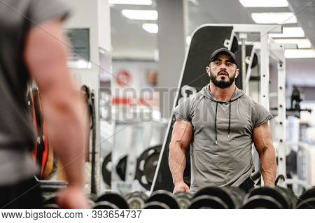 Strong Young Athlete Male With Beard In Sportswear And Great Physique Torso Body Looking At His Refl