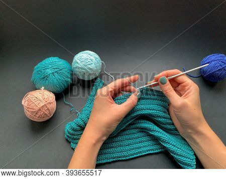 The Process Of Crocheting, Turquoise Thread On A Black Background. A Skein Of Yarn And A Crochet Hoo