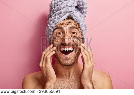 Male Beauty Concept. Happy Joyous Man Applies Coffee Scrub On Face, Removes Dark Dotes, Wants To Loo