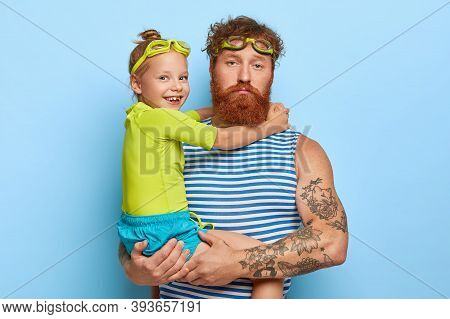 Serious Ginger Man Feels Tired Of Playing With Child, Dressed In Summer Clothing, Wear Swim Goggles,