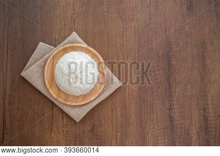 Cooked Jasmine Rice In Wooden Plate With Napkin On Wooden Table. Thai Jasmine Rice.