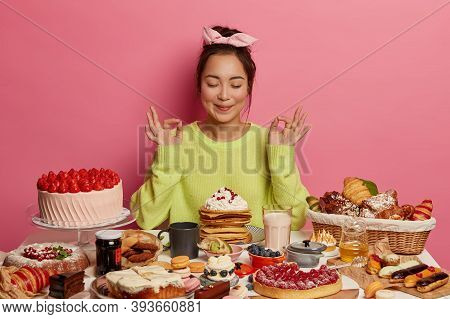 Beautiful Asian Woman Sweet Tooth Meditates And Practices Yoga, Eats Yummy Pancakes And Cakes, Feels