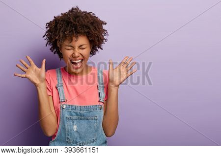 Studio Shot Of Thrilled Joyful Woman With Afro Hairstyle Laughs Out From Something Funny, Raises Pal