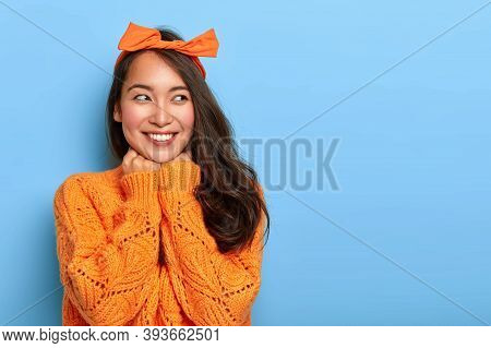 Studio Shot Of Happy Upbeat Woman Wears Bright Orange Knitted Jumper, Bow Headband, Holds Hands Unde