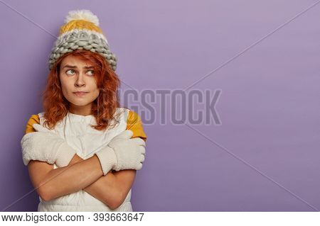 Beautiful Redhead Woman In Wool Knitted Hat, White Gloves And Vest, Crossed Arms Over Body, Trembles