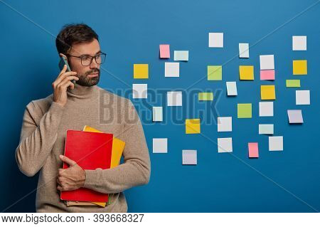 Handsome Bearded Guy Holds Modern Smartphone Near Ear, Discusses Stratup Ideas, Dressed In Comfortab