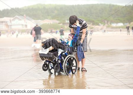 Young Biracial Asian Caucasian Man Pushing Disabled Little Brother In Wheelchair On Beach