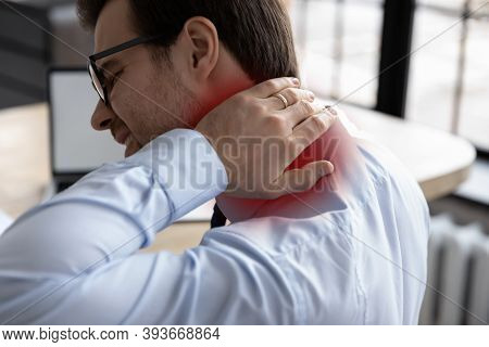 Unhealthy Millennial Male Manager Suffering From Strong Neck Pain.