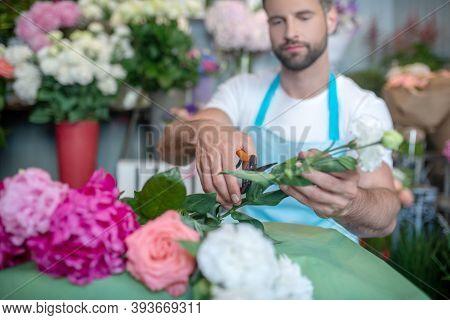 Bearded Florist Cutting Flowers Inside Flower Shop