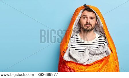 Photo Of Male Hiker Has Sleepy Face Expression, Dressed In Casual Striped Jumper Stands Wrapped In S