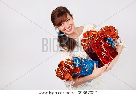 Smiling woman in white dress holds three red and blue boxes with gifts.