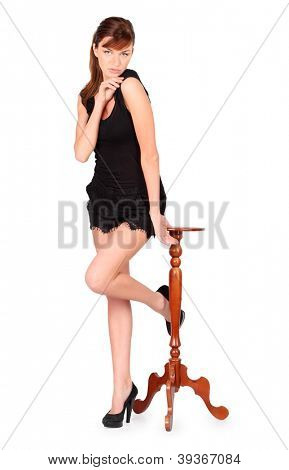 Girl in black dress stands beside small round table isolated on white background.