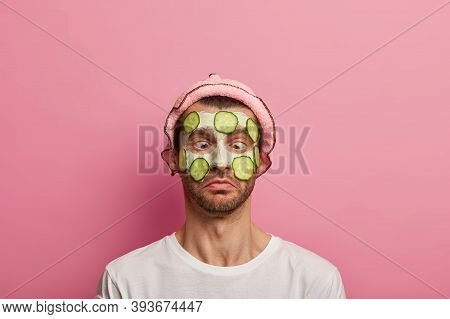 Funny Male Model Has Comic Expression, Crosses Eyes, Wears Clay Mask And Cucumber Slices On Face, So