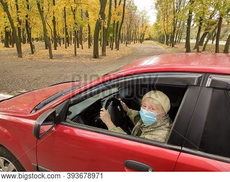 Elderly Caucasian Woman With Her Facemask In The Car. Female Senior Citizen In Mask To Protect Herse