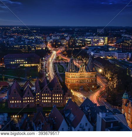 Luebeck, Germany - December 17, 2019:  Aerial Night View Over The Illuminated Holstentor And Histori