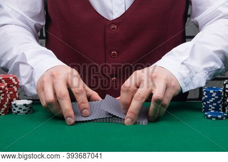 The Croupier's Hands Are Shuffling A Deck Of Poker Playing Cards On The Green Cloth Of The Table