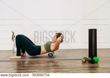 Adult Sporty Woman Doing Fascia Exercise On The Floor. Caucasian Female Using Foam Massage Roller -