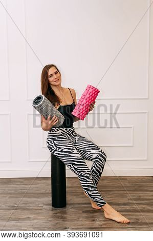 Front View On Caucasian Female Instructor Holding Foam Massage Roller. Young Muscular Fitness Woman