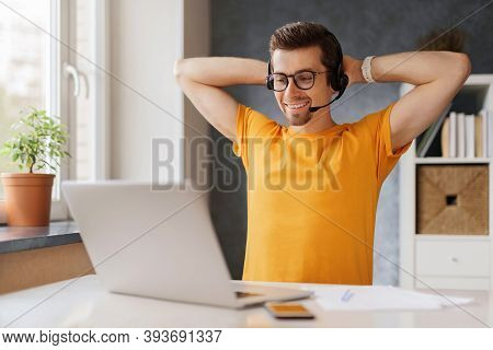 Young Happy Man Sitting At Home Office,smiling, Enjoying Work Or Study Remotely From Home By Interne