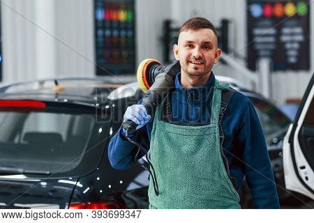 Male Worker In Uniform Polishing New Modern Car. Conception Of Service.