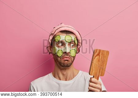 Impressed Young Man Stares At Wooden Mirror, Applies Clay Mask And Cucumbers, Shocked To Have Much W