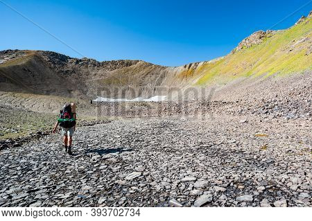 Male Hiker In Dry Mountain Terrain. Young Man Alone Trekking And Backpacking Near Sary Chelek Lake,