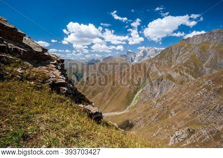 Rocky Pass With Mountain Top Views In High Mountains. Young Men And Women Hiking Near Sary Chelek La
