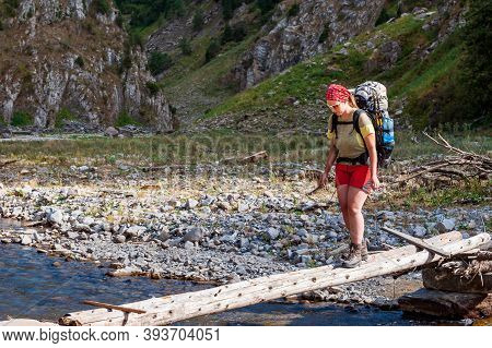 Young Woman Crossing River Stream In High Mountains. Femail Trekker Near Sary Chelek Lake, Sary-chel