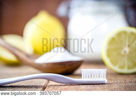 Toothbrush With Glass With Baking Soda And Citrus Fruits Like Lemon Or Orange In The Background. Spo