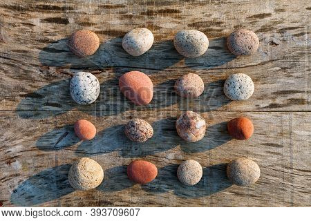 Pattern Of Multicolored Pebbles On A Gray Old Wooden Surface. Spa Decoration. Meditation And Relaxat