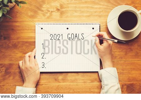 2021 Gaols With A Person Holding A Pen On A Wooden Desk