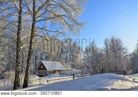 Old Wooden Village House On The Edge Of Winter Forest With Lacy Crowns Of Snow-covered Trees. Beauti