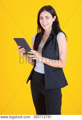 Fashion Smiling Woman Using Tablet. Businesswoman Using Smartphone Over Yellow Background