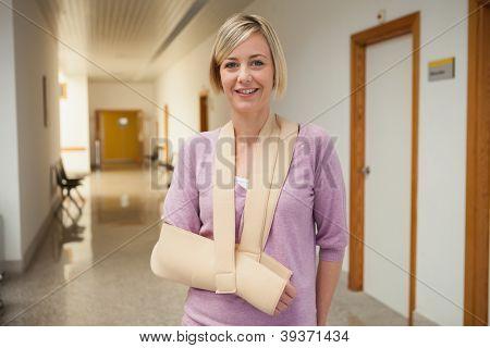Patient with broken arm in sling in hospital corridor