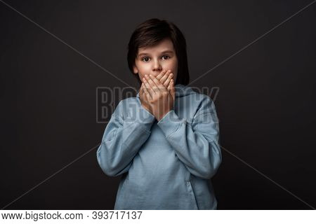 I'm Afraid. Image Of Scared Boy 10-12 Years Old In Casual Clothes Covering His Mouth With Hands. Fri