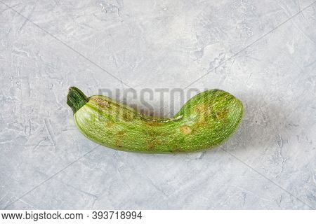 One Spoiled Zucchini On A Gray Background. Ugly Food Concept, Organic Vegetables. Top View, Flat Lay