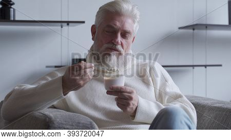 A Handsome Elderly Man With A Gray Beard Eats Yogurt Holding A Spoon Close To His Mouth