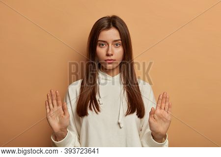 Hold On, Please. Serious Calm European Woman Raises Palms In Stop Gesture, Tries To Sooth Friend, De