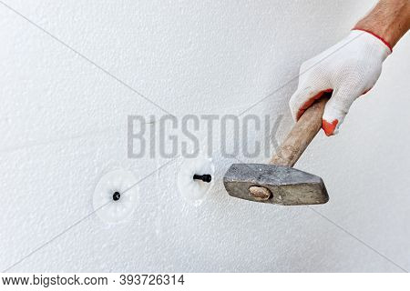 Insulation Of The House With Polyfoam. A Worker Is Using A Hammer For Dowels That Fasten Polystyrene