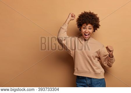 Triumphing Joyful Woman Celebrates Win, Feels Lucky And Upbeat, Yells Yes And Dances Happily, Makes