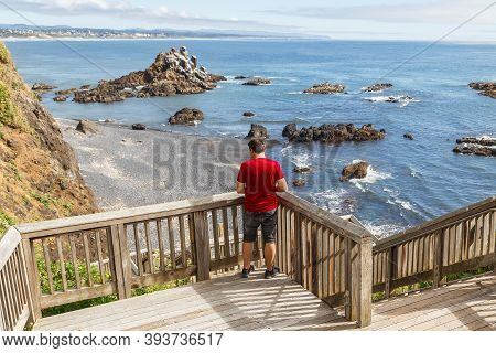 Young Man Standing On Wooden Stairs And Looking Down At Cobble Beach Below Yaquina Head Lighthouse I