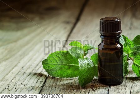 Essential Oil Of Peppermint In A Small Brown Bottle With Fresh Green Mint On An Old Wooden Backgroun